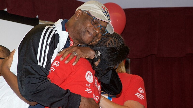Bob Beamon hugs a student who received a pair of donated shoes.