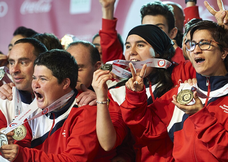 Male and female athletes in a group cheering with medals around their necks.
