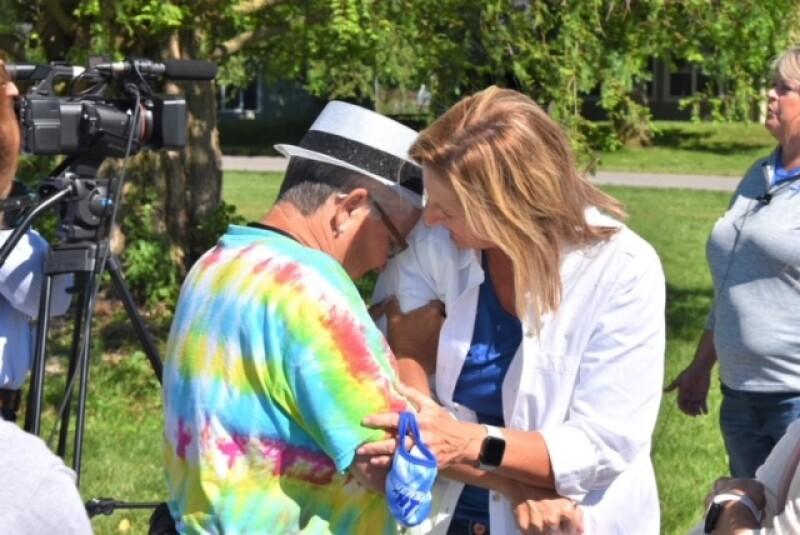 A woman wearing a tie-dye shirt celebrates with a friend.
