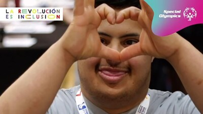 """A Special Olympics athlete who got free health screenings in the Healthy Athletes Program during World Games Abu Dhabi 2019 makes a heart-shaped sign with his hands while looking at camera. Spanish text in front of him reads """"Together, we have the power to make sure nobody is left behind during this critical moment."""""""