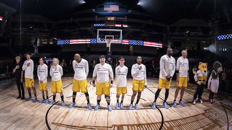 The team in yellow stands at the opening of the game for the Pledge of Allegiance.