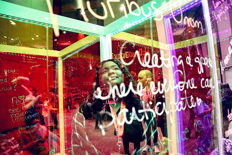Young woman looking up at writings on a glass wall and smiling.