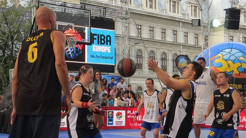 Special Olympics Romania 3x3 basketball activities. Three players from each team are playing in an outdoor facility. Spectators are watching in the background.
