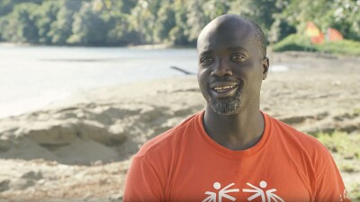 Kester Edwards on the beach speaking in interview wearing a red Special Olympics t-shirt.