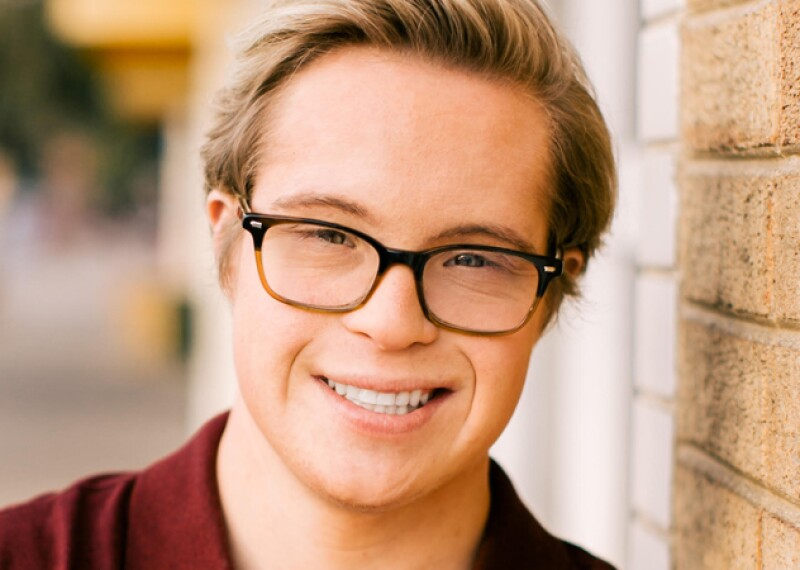 Professional head shot of Cole smiling wearing a burgundy polo.