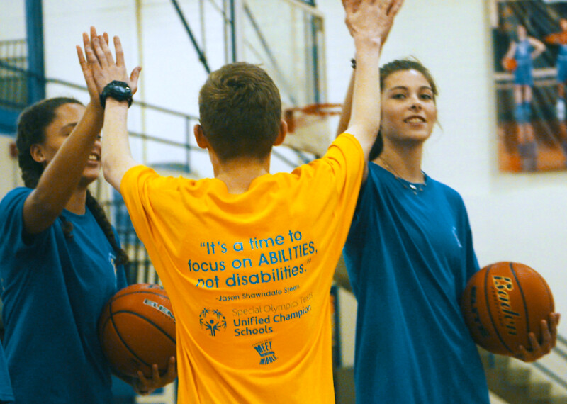 A Unified Student giving a double high five to two other students with basketballs