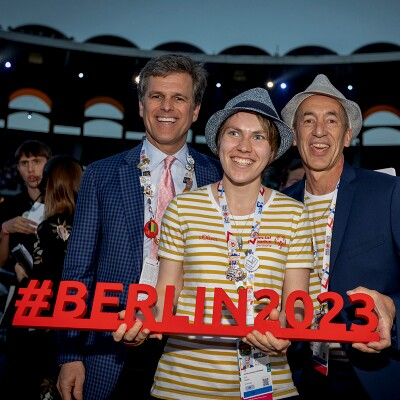 Three people standing together in a group holding a sign that reads: #BERLIN2023