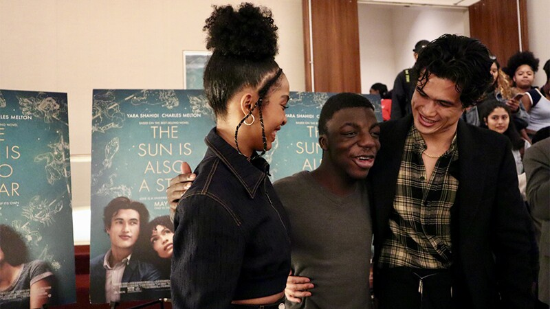 Actors Yara Shahidi and Charles Melton gather around a male Special Olympics New York athlete for a picture.