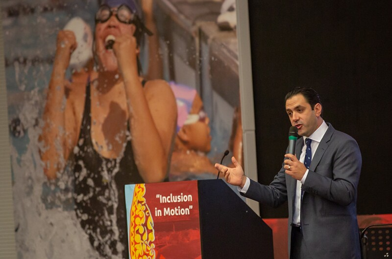 leadership-conferDavid Evangelista, holidng a micraphone and standing behind a podium with text on the front that reads: Inclusion in Motion. He's addresses participants at opening of Special Olympics Europe Eurasia Leadership Conference 2018. A photo in the background is of a young woman splashing out of the water with a look of victory and excitement on her face.
