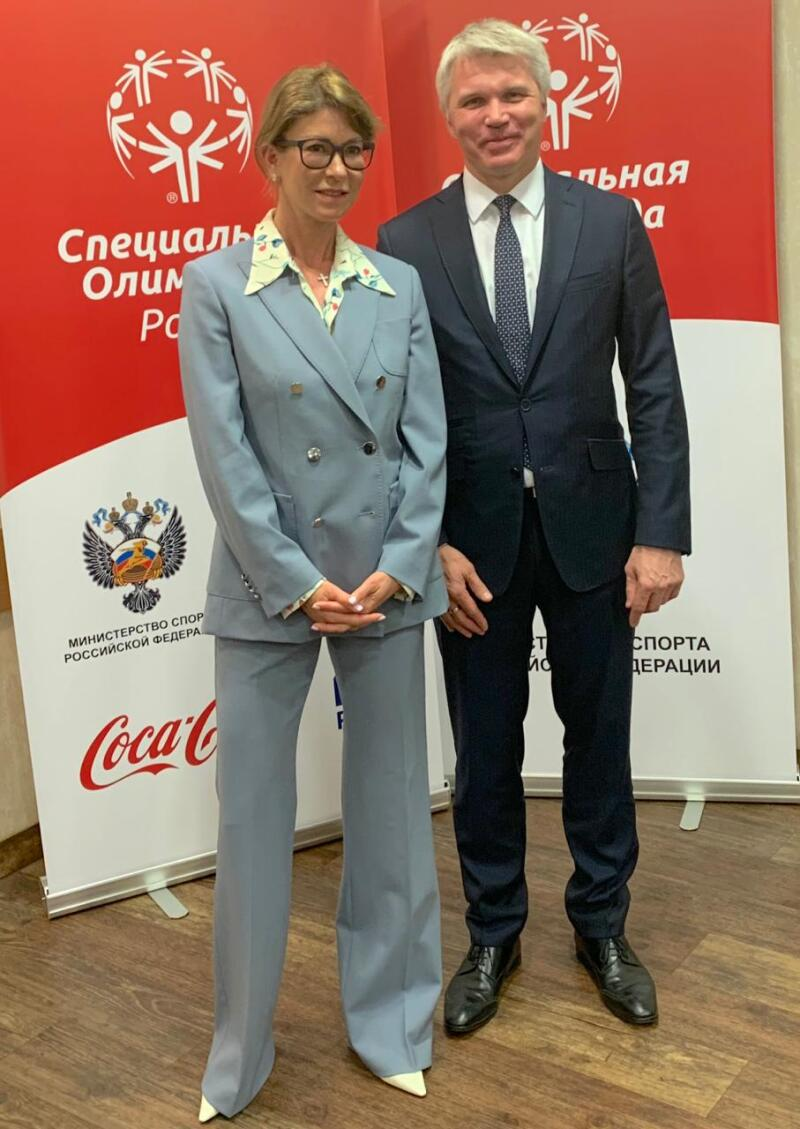 A woman in a blue trouser suit and a man in a navy suit and tie stand side by side facing the camera in from of two Special Olympics Russia pull-up banners.