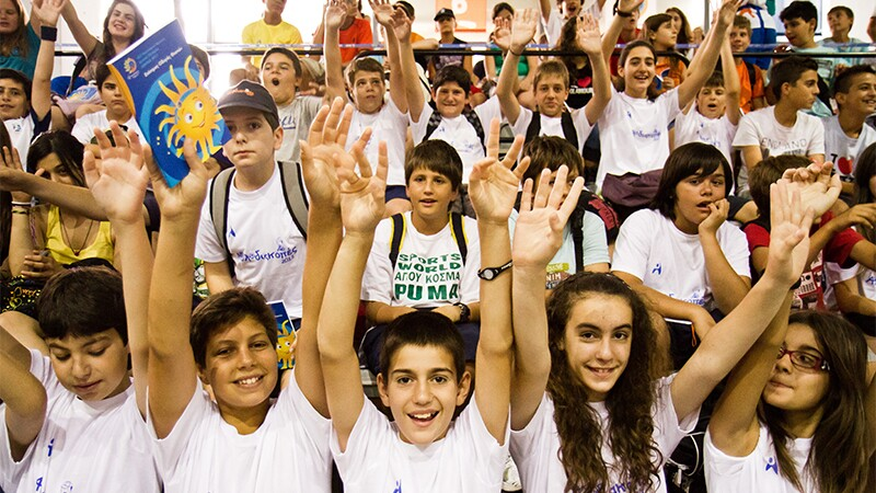 Young adults cheering in an auditorium.