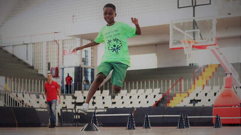 Young athlete jumping through a course in a gymnasium.