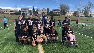 Coach Warner (first on the left) standing with her flag football team on the field.