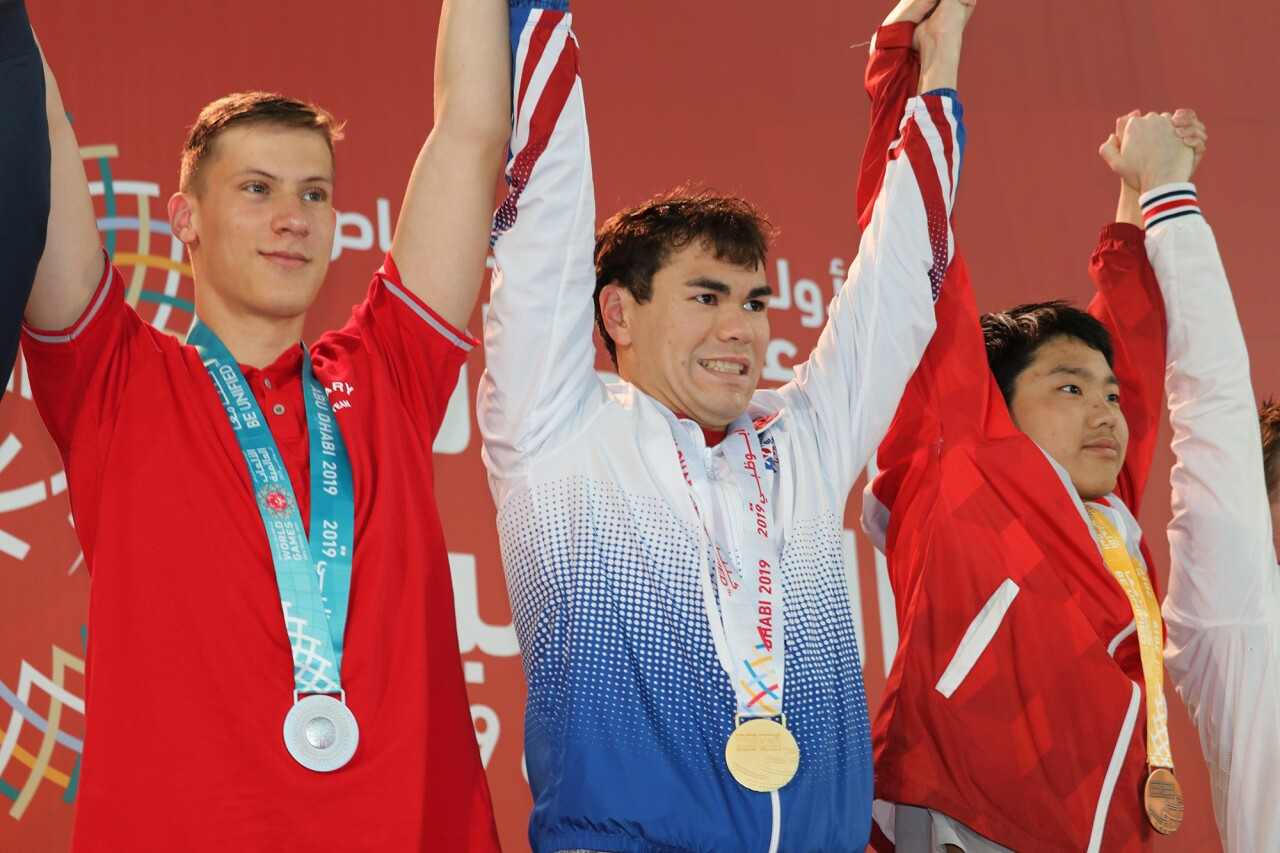 Jonathan placing on the podium with a medal around his neck. An athlete is on either side of him.