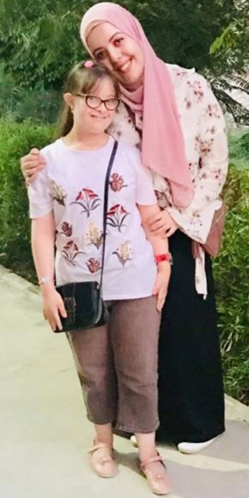 Two young women pose outside together. One woman puts her arm around the other, they both smile.