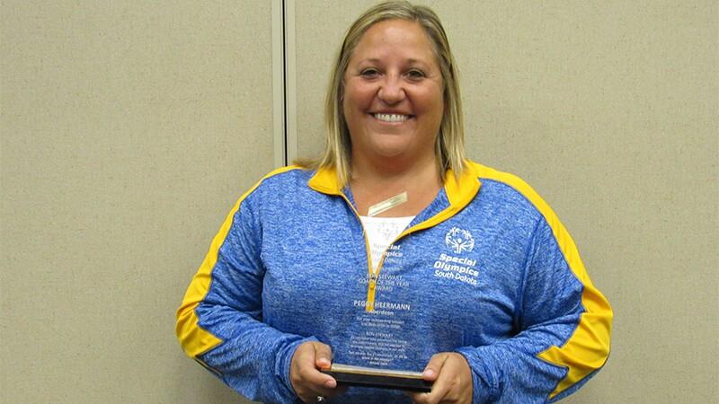 Peggy Heermann holding an award.