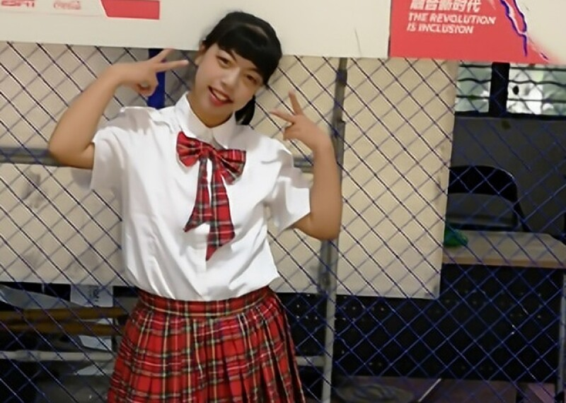 A girl around 14 years old stands inside at school, wearing school clothes. She smiles and gives peace signs with both hands.