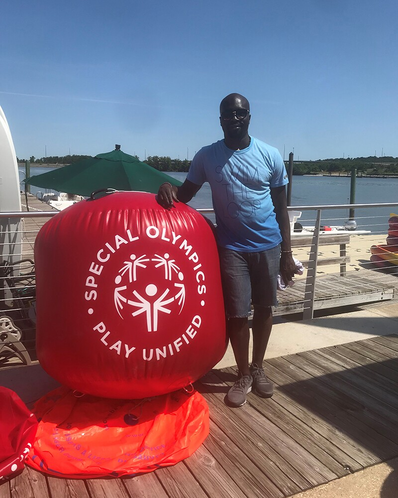 Kester Edwards standing on the dock, next to a Special Olympics Play Unified float.