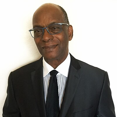 "Robert ""Bob"" Beamon in a black suite and tie with a white and black vertical striped collared shirt."