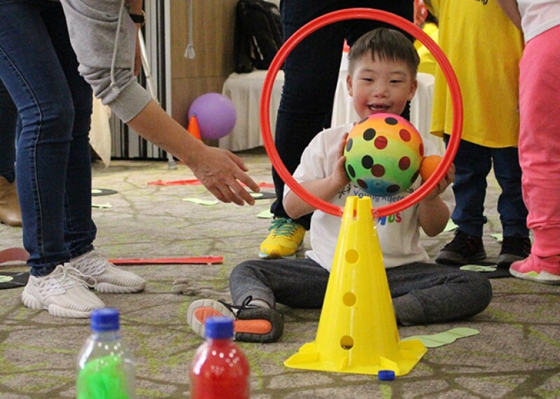 Young athlete from Special Olympics Mongolia is developing his athletic skill during Young Athlete Training workshop. He is sitting on the carpet with his legs bent in front of him holding a multi-colored polka-dot ball preparing to toss it through an orange hoop mounted on a yellow cone. There are more young athletes in the background.
