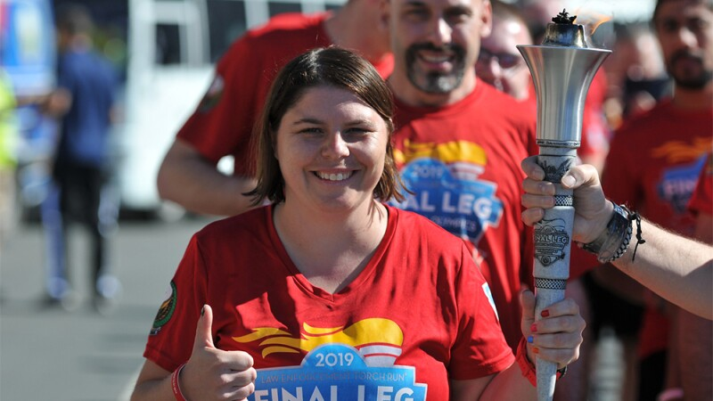 Sherri holds the torch with another runner and gives a thumbs up; other runners can be seen in the background.