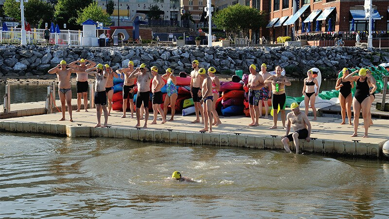 Swimmers standing on the dock preparing to swim, one athlete is already in the water and another is sitting with his feet in the water.