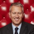 Professional photo of James Quincey sitting on a red high-backed couch.