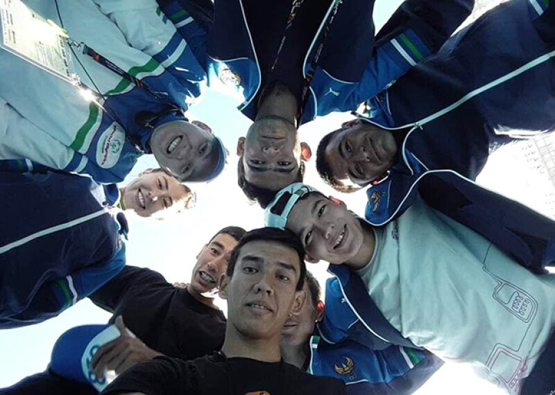 a group of young adults huddled in a circle looking down as the camera looks up at them for a unique photo.