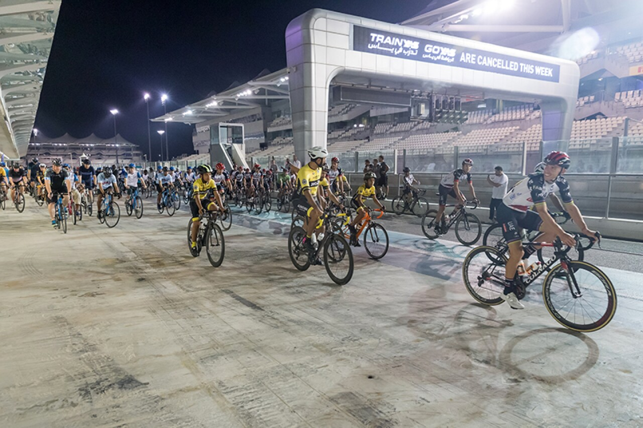 A large group of cyclists start off on their first lap around Yas Marina Circuit.