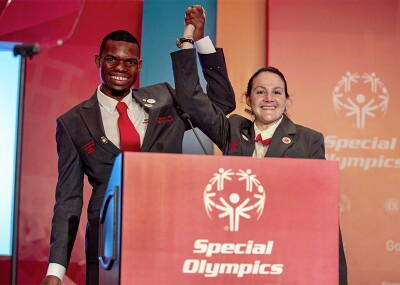 Nyasha and Renee standing behind a podium and holding one another's raised hand.