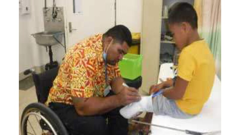 Young male athlete receiving an examination on his amputated leg by a health professional.