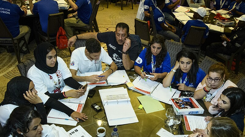 Female leaders from around the globe engage in conversation during the Global Athletes Congress workshop. They all are sitting at a round table talking to one another and looking over and through notebooks.