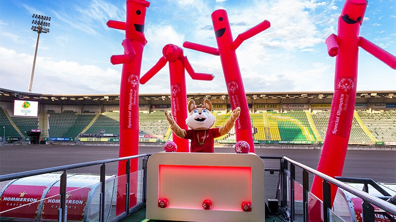 Mascot  DJing on a platform in a stadium.