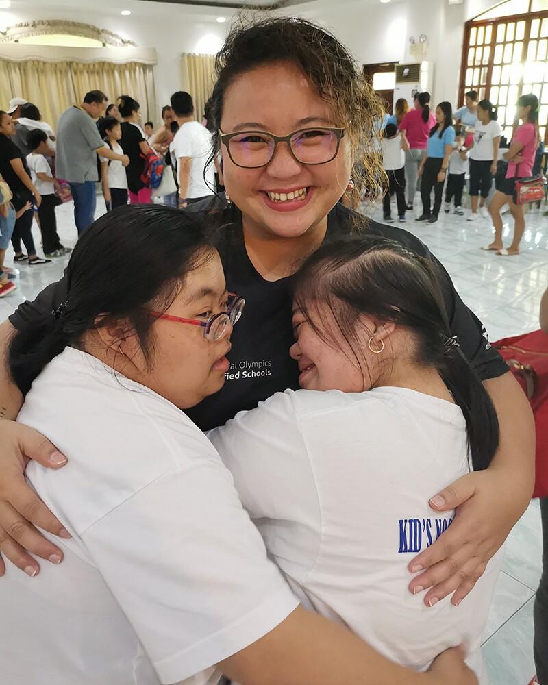 Kaye Hugging two young girls.
