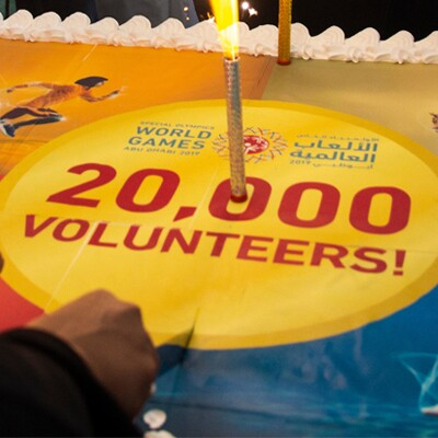 A cake that has a candle that reads 20,000 volunteers