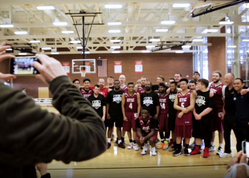 photographer taking a photo of a unified tam on the court.