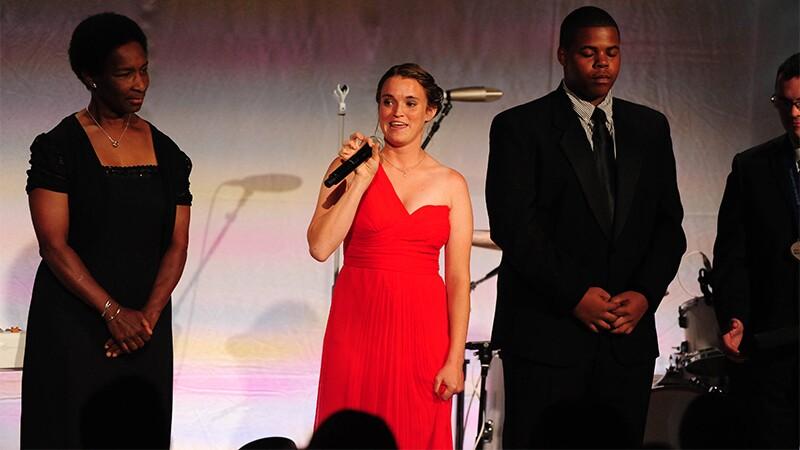 Athlete Loretta Claiborne and Danielle Liebl (speaking) accompanied by Kenny Brown.