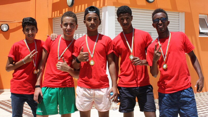 Five athletes in red shirts standing side by side with medals around their necks.