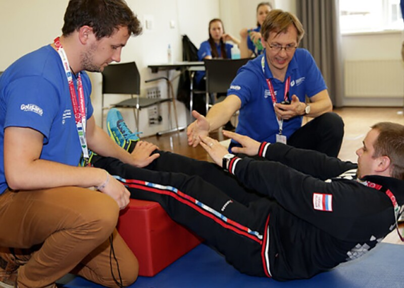 Athlete performing sit-ups during health screening while two volunteers assist and observe.