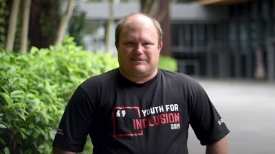 """Benjamin Haack standing outside wearing a shirt that reads, """"Youth for Inclusion 2019"""""""