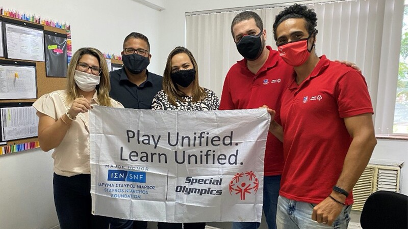 Five people dressed professionally, wearing masks, stand together. Two wear red Special Olympics polos. They all hold a banner with the logos of the Stavros Niarchos Foundation and Special Olympics.