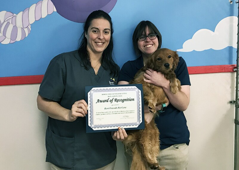 Katy Sanchez (R) is holding a small dog and standing next to a colleague that is presenting Katy with an Award of Recognition.