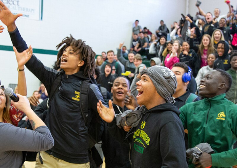A group of excited students in a gymnasium are reaching for a baton as spectators watch from the bleacher in the background.