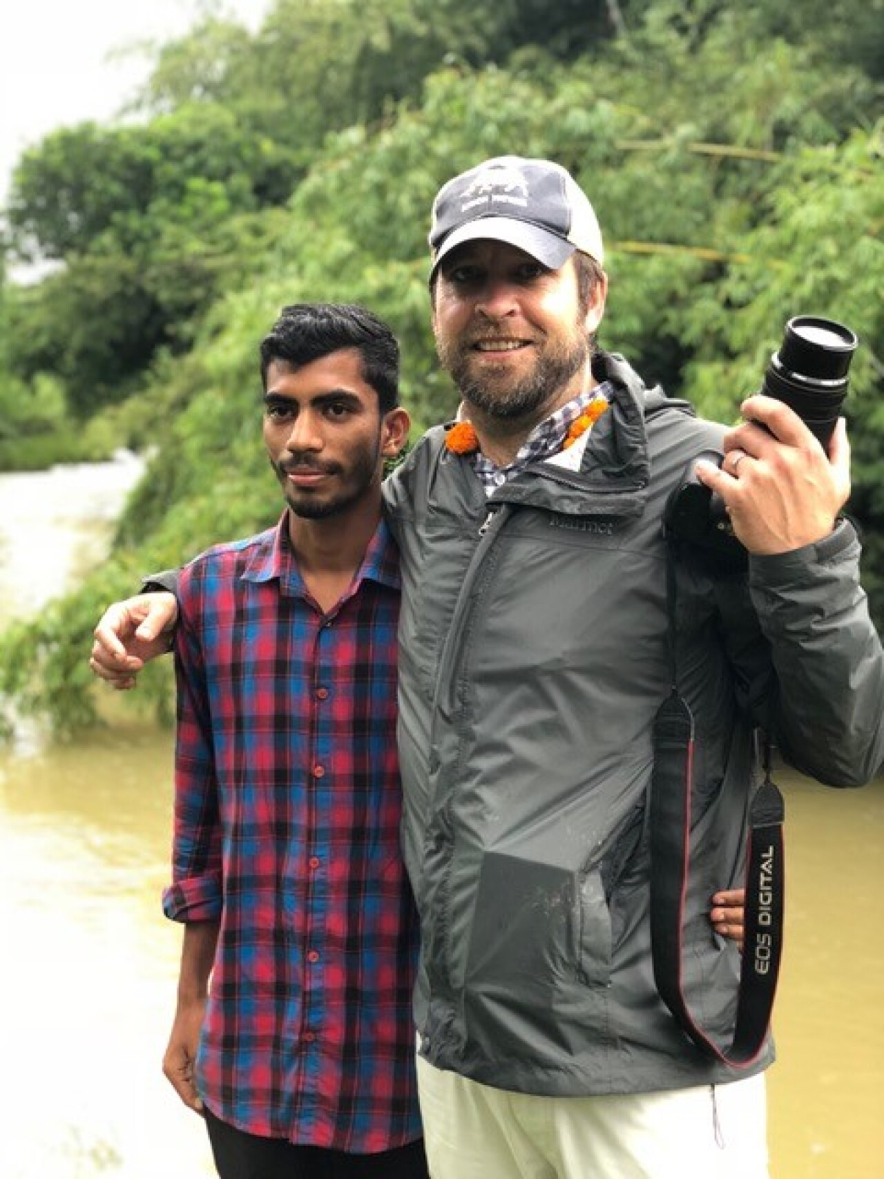 A photographer and a man smile and pose for a photo. They are standing in front of a small lake or stream with lush green shrubbery on the banks.