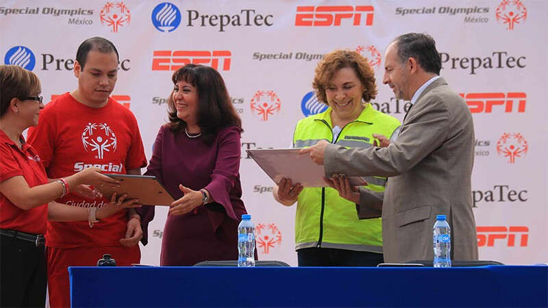 Special Olympics, school, and other representatives stand on stage presenting awards and plaques. in the background is PrepaTec, ESPN, and Special Olympics Mexico signage.