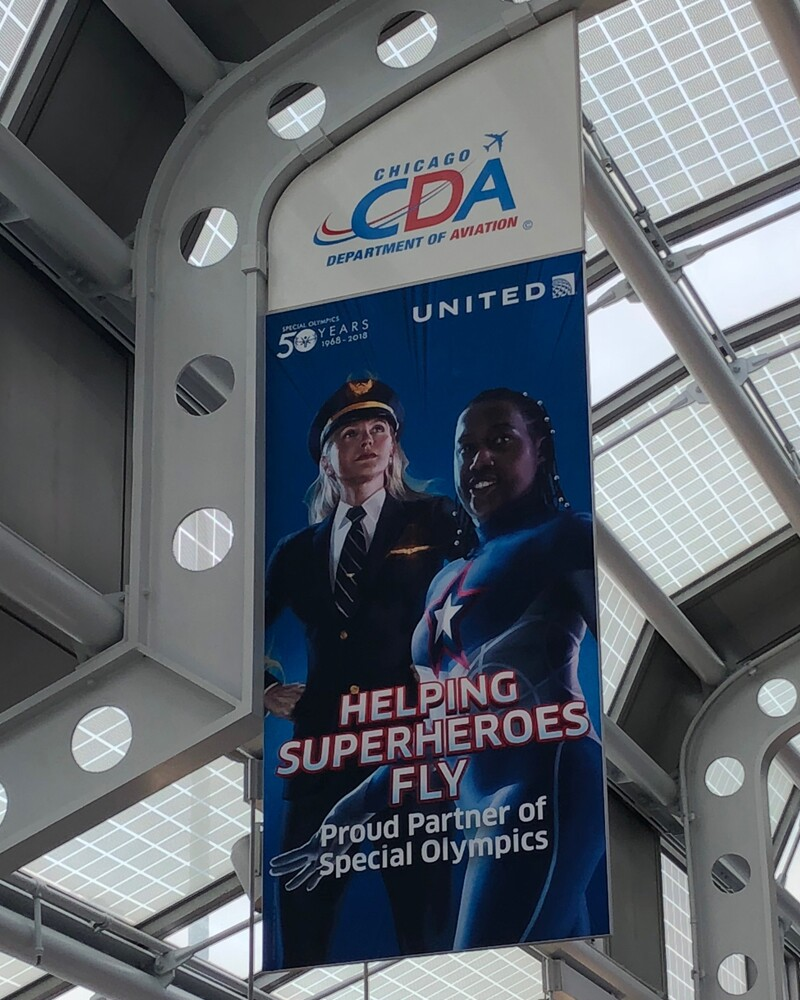 "Novie is on a large banner in an airport. The banner is an advertisement for United and says ""Helping Superheroes Fly. Proud Partner of Special Olympics."" She is wearing a superhero costume next to a United pilot."