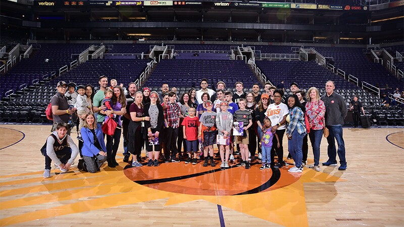 Devin Booker poses for a large group photo during a meet and greet for children with 22q11.2 and their families.