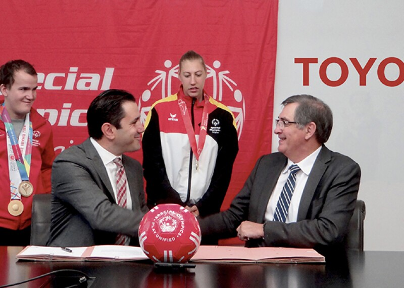 Two men sitting at a table shaking hands; the signing in the back ground (left) reads: Special Olympics; the signage in the background (right) reads: Toyota