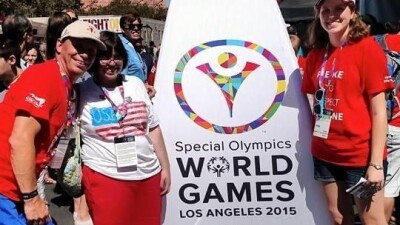 Three people pose in front of a large white sign that has the Special Olympics World Games LA 2015 logo on it. They are smiling.