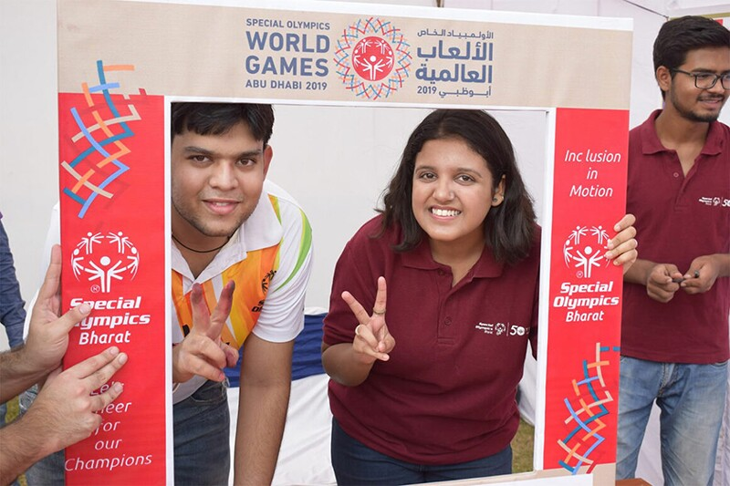 Athlete and volunteer standing behind a decorative fraom from the Special Olympics World Games Abu Dhabi 2019 posing together for a photo.